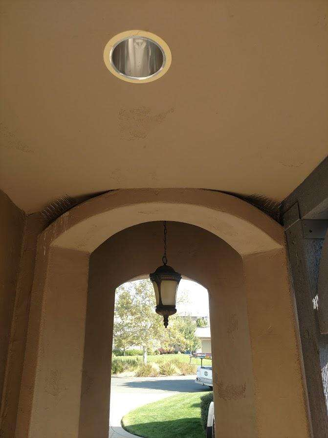 The light fixture is above the hanging light, within the entry area.