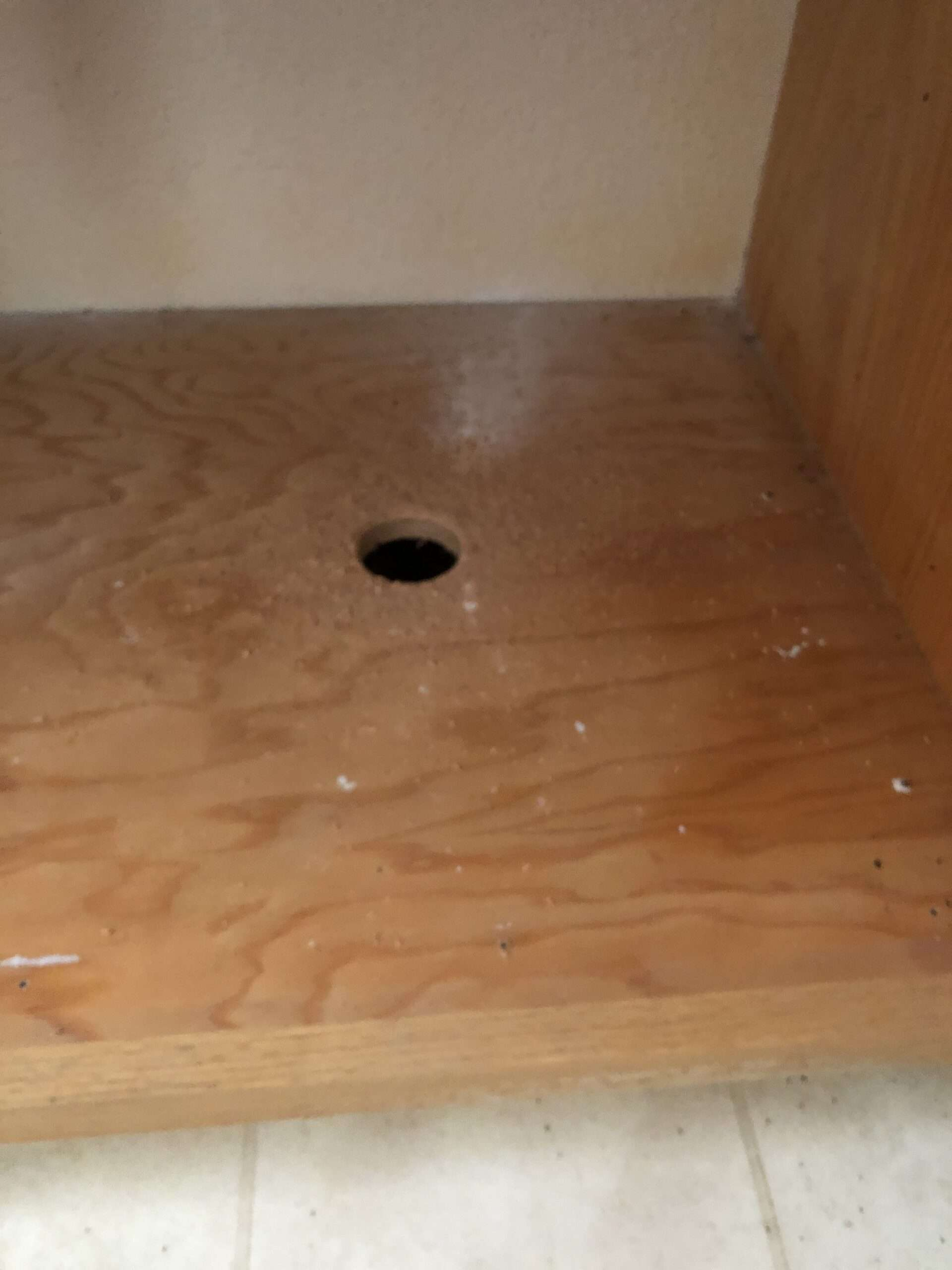 Homeowner cut access hole in bottom of cabinet.